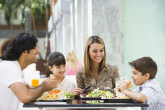Family enjoying lunch at cafe. Family enjoying meal sitting at cafe table Stock Photography