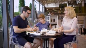 Family is enjoying the meal all together in the restaurant, laughing and chatting with each other stock footage