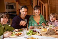 Family Enjoying Meal In Alpine Chalet Together Stock Image