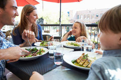 Family Enjoying Meal At Outdoor Restaurant Royalty Free Stock Images