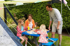 Family Enjoying Meal Outside Tent On Camping Holiday. Smilling royalty free stock photography