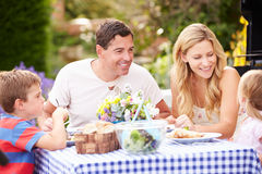 Family Enjoying Outdoor Meal In Garden Stock Image