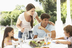 Family Enjoying Outdoor Meal In Garden Together Stock Photos