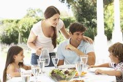 Family Enjoying Outdoor Meal In Garden Together Stock Photos