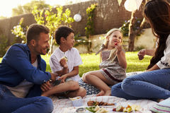 Family Enjoying Picnic On Blanket In Garden Royalty Free Stock Photography