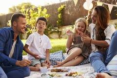 Family Enjoying Picnic On Blanket In Garden Royalty Free Stock Images