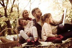 Family enjoying on picnic together. Father reading book to his little girl stock photography