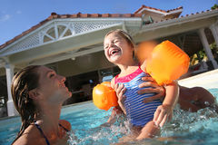 Family enjoying in the pool. Family playing in swimming pool of private villa Stock Photography