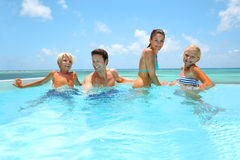 Family enjoying pool time. Family of four bathing in swimming pool Royalty Free Stock Photos