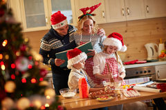 Family enjoying preparing Christmas cookies Stock Images