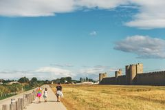 Family enjoying promenade around famous fortification wall surrounding Aigues-Mortes city Stock Photos