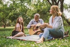 Happy family playing guitar in their green park garden. Family enjoying quality time, playing guitar in their green park garden stock photo