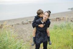 Family enjoying the rain and having fun outside on the beach a gray rainy. Family two enjoying the rain and having fun outside on the beach on a gray rainy stock photo