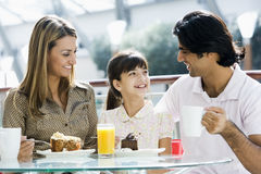 Family enjoying snack at cafe. Family eating piece of cake in cafe Stock Images