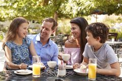 Family Enjoying Snack At Outdoor Caf� Together stock image