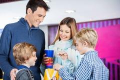 Family Enjoying Snacks At Cinema Stock Image