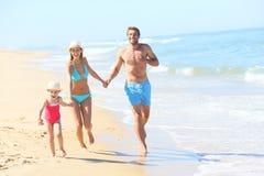 Family enjoying summer holidays on the beach Stock Photos