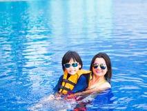 Family enjoying summer vacation in luxury swimming pool.  Stock Image