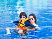 Family enjoying summer vacation in luxury swimming pool.  Royalty Free Stock Images