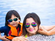 Family enjoying summer vacation in luxury swimming pool.  Royalty Free Stock Photography