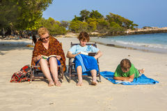 Family is enjoying the sun and relaxing and reading books at the. Beautiful beach Stock Photos