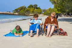 Family is enjoying the sun and relaxing and reading books at the Royalty Free Stock Image