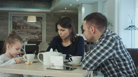 Family Enjoying tea In Cafe Together. Father and mother talking looking at their daughter. stock video