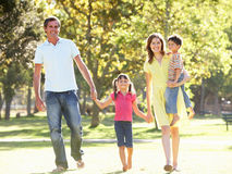 Family Enjoying Walk In Park. Smiling At Camera Royalty Free Stock Image