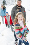 Family Enjoying Walk Through Snowy Landscape Royalty Free Stock Photos