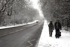A family enjoying a winter stroll in a heavy fall of snow Royalty Free Stock Photo