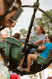 Family Enjoys Carnival Ride At County Fair Stock Photo