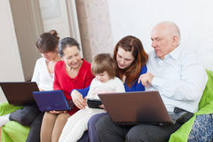 Family enjoys  with few laptops at home Royalty Free Stock Photography