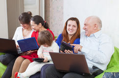 Family enjoys on sofa with few laptops Stock Photos