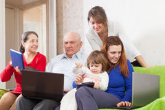 Family enjoys on sofa with  laptops Stock Photos