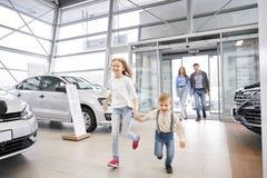 Family entering car dealership, happy children running. Cheerful parents entering car dealership showroom, Happy children running, holding hands and smiling royalty free stock photo