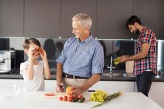 The family is entertained by preparing a salad for Thanksgiving. The old man is cooking, the boy is fooling around Stock Photos