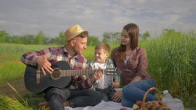Family entertainment, happy guy plays musical instrument while girl with child sing and clap while relaxing on picnic on. Open air in green grass close-up stock footage