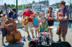 Family entertainment on the waterfront on Canada Day in Victoria BC. A family of musicians and singers entertains the crowds on Canada Day in the capital city of Royalty Free Stock Photos