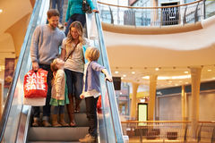 Family On Escalator In Shopping Mall Together. Looking At Each Other Smiling stock images