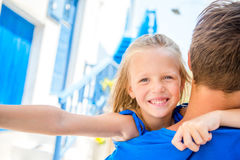 Family in Europe. Little adorable girl taking self portrait with her father in Mykonos streets during summer greek Stock Image