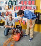 Family Examining Air Compressor In Store Royalty Free Stock Image