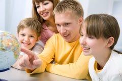 Family examining a globe Stock Images
