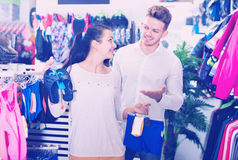 Family examining various swimsuits for children in sports store. Smiling happy cheerful family examining various swimsuits for children in sports store stock photo
