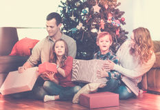 Family exchanging Christmas gifts. Large family exchanging gifts during Christmas at home and smiling royalty free stock images