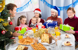 Family exchanging Christmas gifts. Family members handing gifts to each other during Christmas dinner Stock Image