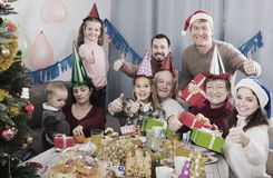 Family exchanging Christmas gifts. Smiling family members handing gifts to each other during Christmas dinner Stock Image