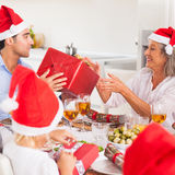 Family exchanging christmas presents. Around the dinner table wearing santa hats Royalty Free Stock Image