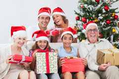 Family exchanging christmas presents. Happy family exchanging gifts at christmas time on the couch Royalty Free Stock Images