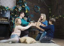 Family exchanging gifts in front of Christmas fir-tree Stock Photos