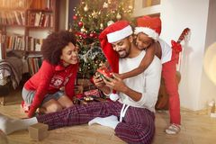 Family exchanging gifts in front of Christmas tree. At home stock photos